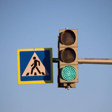 Green traffic light and pedestrian crossing sign over the Russian road against a blue sky