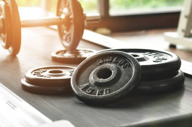 dumbbell and barbell on floor at gym