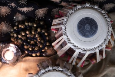 Tabla, Indian classical drums with foot cymbals - Ghungroo - in an ornate setting with traditional Indian rustic jewellery and beads.