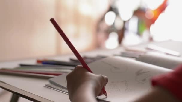 Ruka z malé holčičky barvuje obrázek v knize s barevnou tužkou na psacím stole, Art a vzděláním.