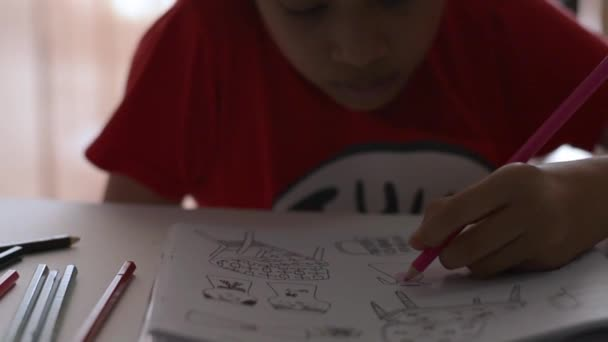 Holčička obarvuje obrázek v knize s barevnou tužkou na stole, výtvarného umění a vzdělání.