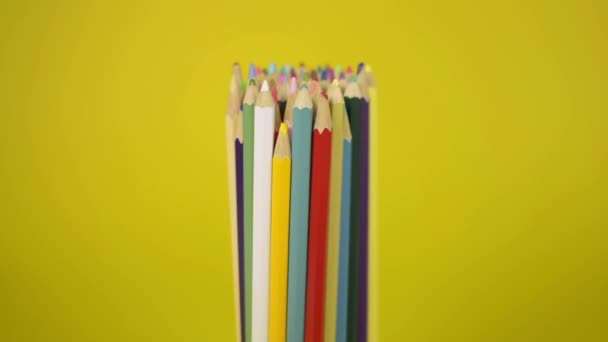 Colored pencils that are tied together are fall disorderly on yellow background, Unity and cooperation of organization concept.