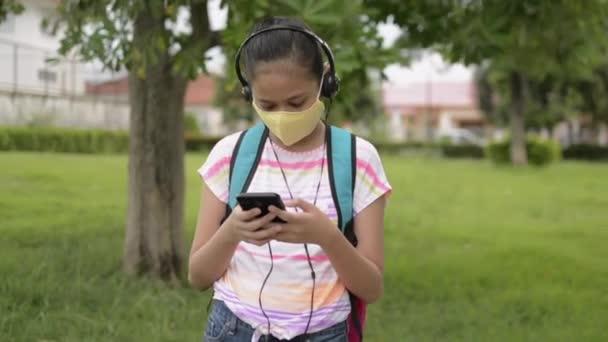 Asiatische Grundschülerin mit Schutzmaske, Kopfhörer tragend und im öffentlichen Park stehend. Teenager mit Rucksack und Handy im Wohngebiet. Coronavirus-Schutz. Drehschuss.