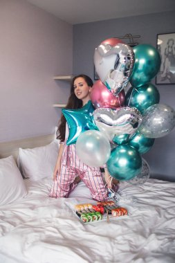 Birthday party. Beautiful young girl in pajamas on bed with balloons and sushi.