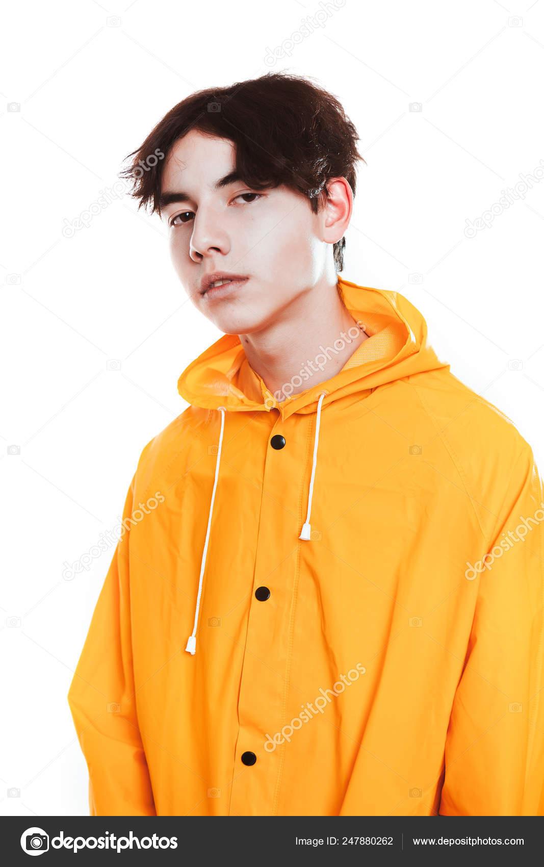 Retrato de un chico adolescente en una morena de impermeable amarillo en el  estudio — Foto
