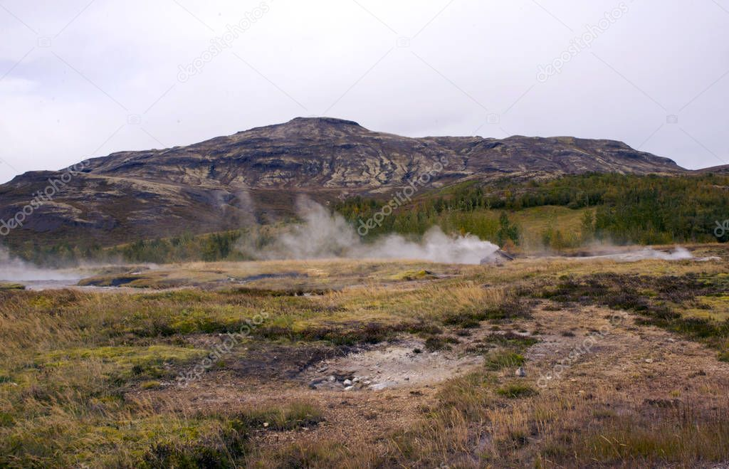 Beautiful view of the national park in the valley of Haukadalur, Iceland. View of the valley of geysers, hills and mountains, smoking sources.
