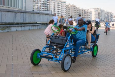 Ostend, Belgium, August 2019. Friendly multi-ethnic family riding a blue multi-seat bicycle. The beautiful promenade of Ostend. A fun trip.