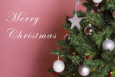 decorated Christmas tree on pink wall background and merry christmas lettering