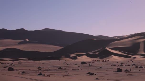 Jeli na velbloudech v poušti. Velbloudí karavana v západu slunce vzdálené shot