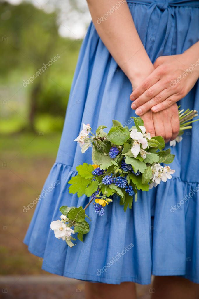 Close-up of womans hand holding a branch of blooming apple tree. Blues dress as a background.Spring concept
