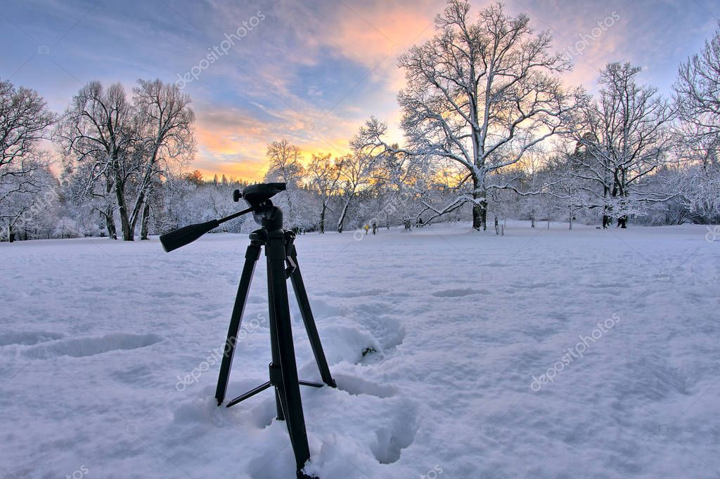 Behind the scenes of a photoshoot of landscape photographer. Capturing of a stunning winter sunset in the snowy forest. Tripod still standing in the snow.