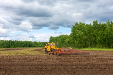 tractor or machine plows the field, harrow and cultivate the soil for sowing grain. concept of agriculture and husbandry