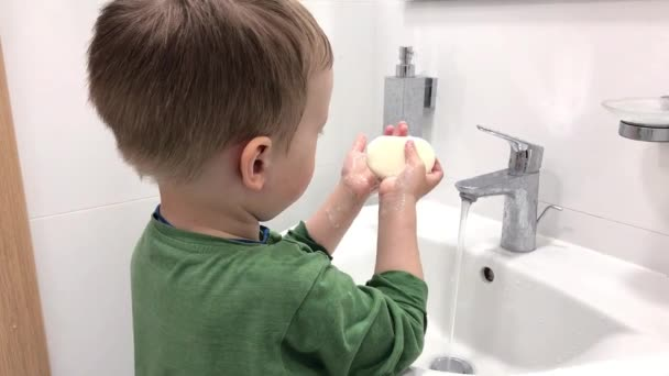 Washing hands in the bathroom. Small child washing his hand under the running water in the bathroom