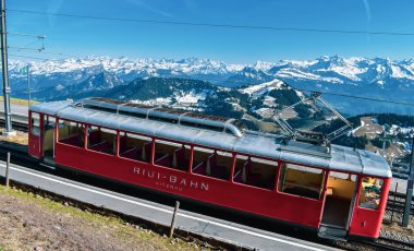 Swiss mountain railways and spring panoramic view of snow-capped mountains in the Alps.