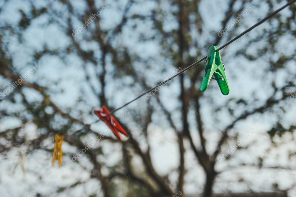 Colorful plastic clothespins on a rope.