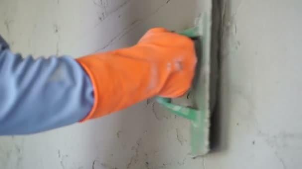 Stavební dělníci omítky zdi pomocí cementu na staveništi