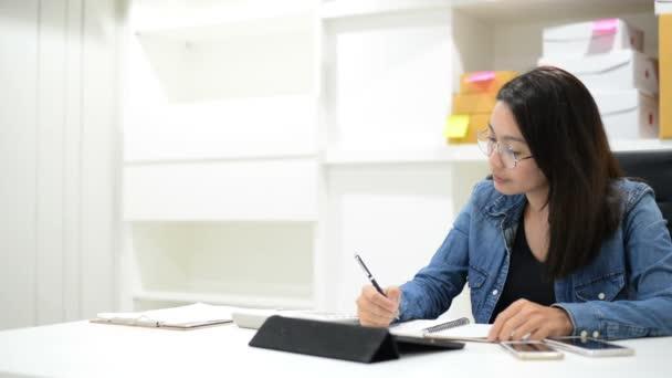 Obchodní žena kontrolu pořadí účty a dělá rozpočet s kalkulačkou a balení doručení krabic