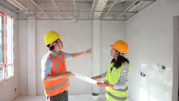 Dvě stavební inženýři pracují společně v boční budově, plánování pro strop