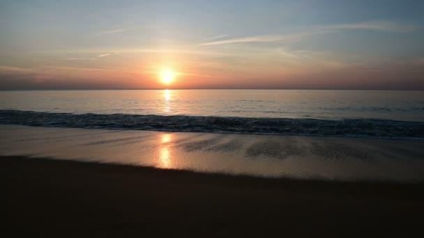 Zpomalené vlny narážely na písečné pláži v západu slunce