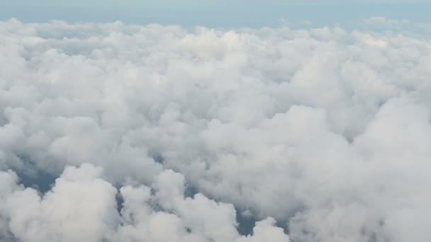 4 k letecký pohled nad mraky z okna letadla s modrou oblohou