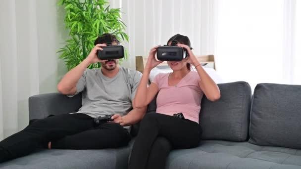 4K Fiatal boldog pár játszik videojátékok viselő virtuális valóság szemüveg
