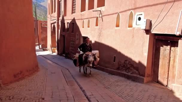 ABYANEH, IRAN - OCTOBER 23, 2017: The senior farmer rides the donkey along the narrow street with red clay houses of traditional mountain village, on October 23 in Abyaneh