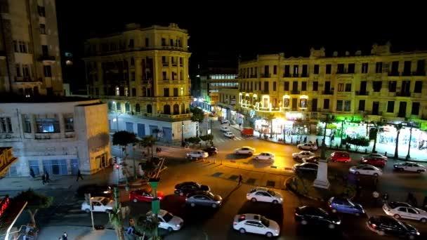 Káhira, Egypt - 23 prosince 2017: Hodinky večer život města - rychlé přenosy na Talaat Harb náměstí s chaotickou pěší pohyb, Svítící okna obchodů a kaváren, na 23 prosinci v Káhiře