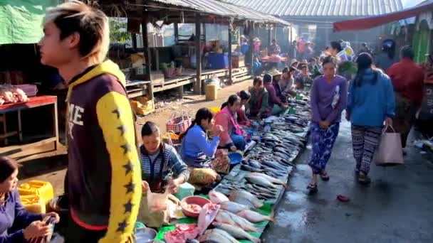 NYAUNGSHWE, MYANMAR - FEBRUARY 20, 2018: The busy morning in Mingalar Market - fish sellers offer fresh catch, clients walk along the market alley and choose foods, on February 20 in Nyaungshwe.