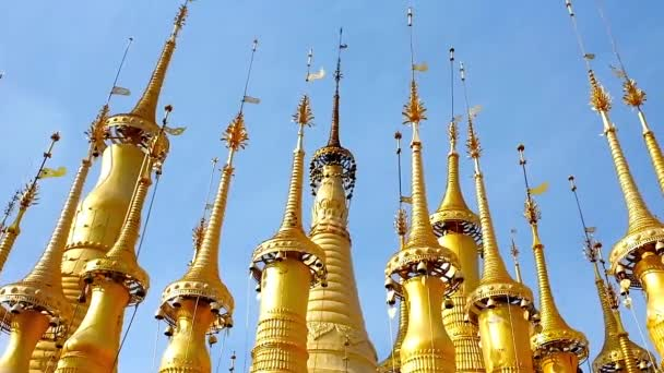 Ornate golden hti umbrellas with ringing bells decorate the medieval pagodas of Inn Thein Buddha Image Shrine, located in the same named village on Inle Lake, Myanmar.
