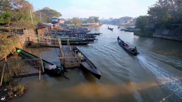 NYAUNGSHWE, MYANMAR - FEBRUARY 20, 2018: The busy canal in tourist village with numerous canoe boats, moored at the banks or floating in different directions, on February 20 in Nyaungshwe.