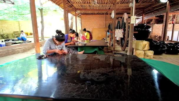 BAGAN, MYANMAR - FEBRUARY 25, 2018: Authentic lacquerware workshop with numerous workers, creating pictures, tableware and souvenirs in unique technique, popular in region, on February 25 in Bagan.