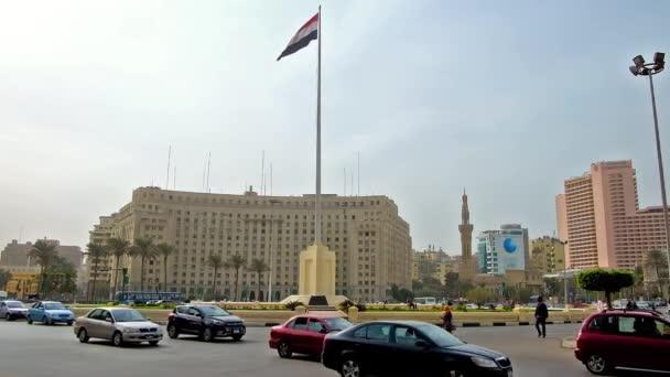 Káhira, Egypt - 24 prosince 2017: Obří vlajka mávala uprostřed rušné Mídán Al Tahrír (mučedníků náměstí) s výhledem na administrativní budově na pozadí, na prosinec 24 v Káhiře