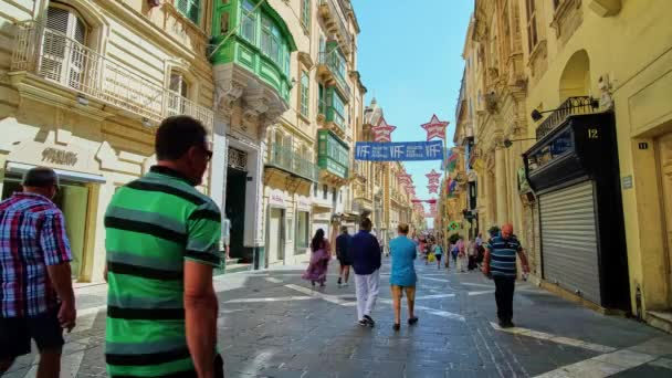VALLETTA, MALTA - JUNE 17, 2018: The crowded central city street -  Triq Ir-Repubblika (Republic), decorated due to the Film Festival, numerous stores, cafes and bars located in historical medieval mansions on both sides, on June 17 in Valletta.