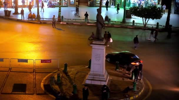 CAIRO, EGYPT - DECEMBER 23, 2017:  Pedestrians chaotically cross the road in Talaat Harb Square with a monument in the middle, on December 23 in Cairo.