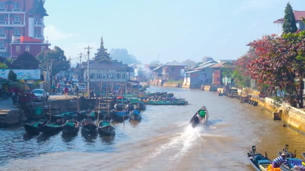 NYAUNGSHWE, MYANMAR - FEBRUARY 20, 2018: Busy harbor of village with numerous tourist and fishermen's canoes, residential houses and Buddhist Temple on the canal banks, on February 20 in Nyaungshwe