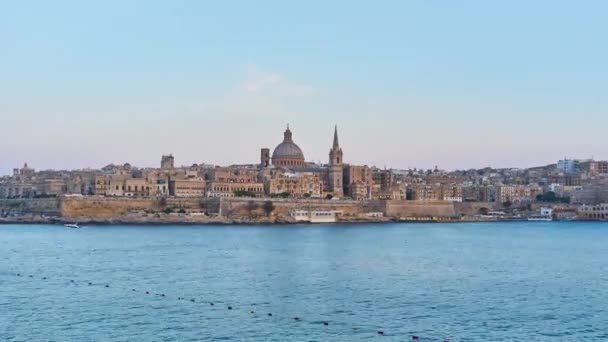 Sliema seaside promenade opens a view on ships and boats, medieval Valletta skyline with tall bell tower of St Paul's Anglican Pro-Cathedral and dome of Carmelite Church behind the tall rampart, Malta