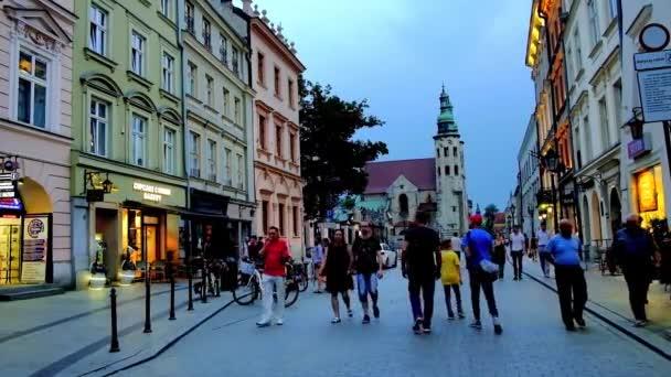 Krakov, Polsko – 10. června 2018: Večerní procházka podél obchodů a kaváren v pěší ulici Grodzka, s výhledem na jeden z nejstarších městských památek - kostel Saint Andrew, 10. června v Krakově
