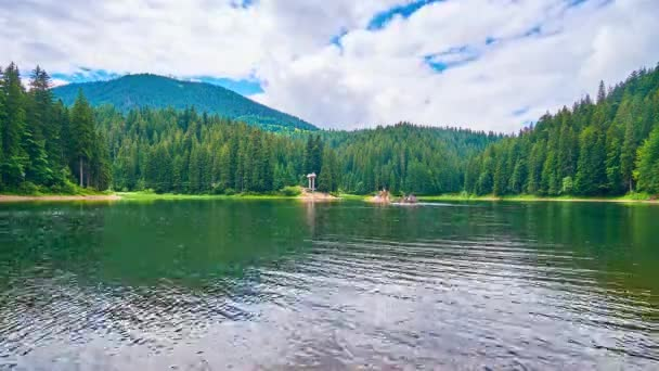 The picturesque Synevyr Lake is surrounded by coniferous forests and Carpathian mountains, the clear surface reflects fast flowing clouds, the tourists enjoy the trip on wooden rafts, Ukraine.
