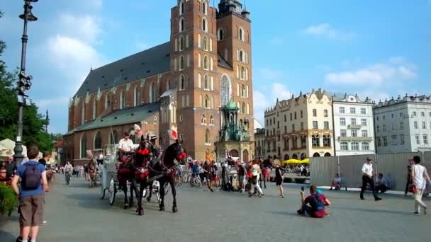 KRAKOW, POLAND - JUNE 11, 2018: Plac Mariacki (Main Market Square) with riding horse-drawn carriages, walking tourists, crowded outdoor cafes and St Mary Basilica on background, on June 11 in Krakow.