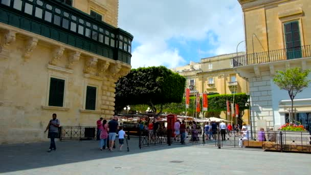VALLETTA, MALTA - JUNE 17, 2018: , The narrow pass between St George Square and Republic Square with a corner of Grandmaster's Palace and numerous outdoor cafes on background, on June 17 in Valletta.