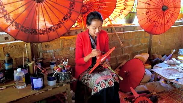 PINDAYA, MYANMAR - FEBRUARY 19, 2018:  Young artisan covers traditional handmade Burmese umbrella with beautiful floral pattern, sitting in showroom of the paper workshop, on February 19 in Pindaya