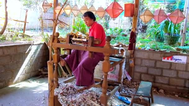 PINDAYA, MYANMAR - FEBRUARY 19, 2018:  The woodworker produces the bamboo handles for paper parasols, using foot-operated wood turning lathe in traditional workshop, on February 19 in Pindaya.