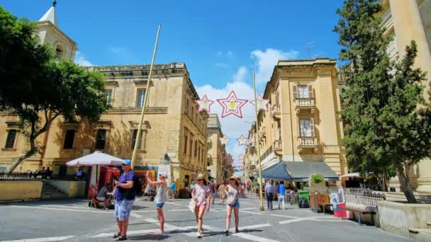 VALLETTA, MALTA - JUNE 17, 2018: Architectural ensemble of Republic Square with a view on crowded Republic street, lined with historical edifices, on June 17 in Valletta.
