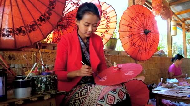 PINDAYA, MYANMAR - FEBRUARY 19, 2018:  The Shan paper workshop's master shows the art of creating traditional Burmese umbrellas, covered with beautiful floral patterns, on February 19 in Pindaya