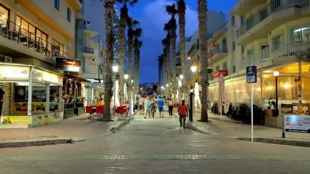 Buġibba, Malta - 14. června 2018: The Bay je náměstí obklopeno gurmánské ulice, plná restaurací a kaváren, malé, nabízí chutné rybí kuchyně, sendviče a chladné nápoje, na 14 června v Buġibbě