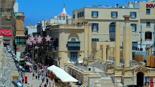 VALLETTA, MALTA - JUNE 18, 2018: Busy square in front of the ruins of Royal Opera House with columns, the crowd of people walks along Republic street, lined with old edifices, on June 18 in Valletta.