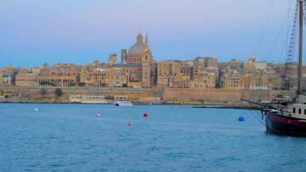 The twilight above the medieval city of Valletta with a view on its architecture, Northern Harbour and ferry, floating to Sliema, Malta.