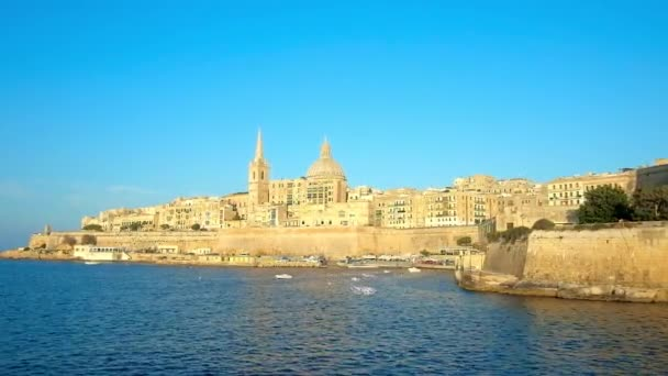 The medieval native limestone Valletta walls, edifices, St Paul's Anglican Pro-Cathedral and Carmelite Church, lighted with sun rays, become shiny golden, Malta.