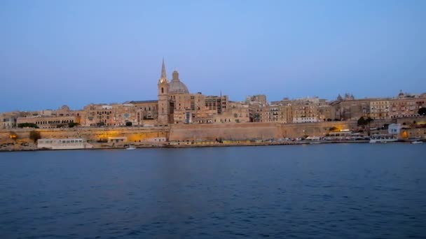 Romantic evening yacht trip along Valletta Northern Harbour with a view on its stunning medieval skyline in soft lighting on blue hour, Malta.