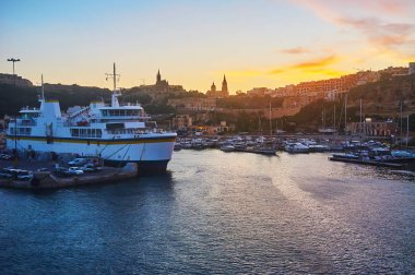 Enjoy the sunset over Ghajnsielem from the sea with a v iew on city hills, Mgarr Harbour and ferry, moored at the shore, Gozo, Malta.